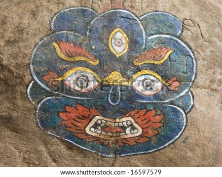 A painting of Kala Bhairava (one form of the Hindu god Shiva) painted on a rock on a pilgirmage path in Nepal.