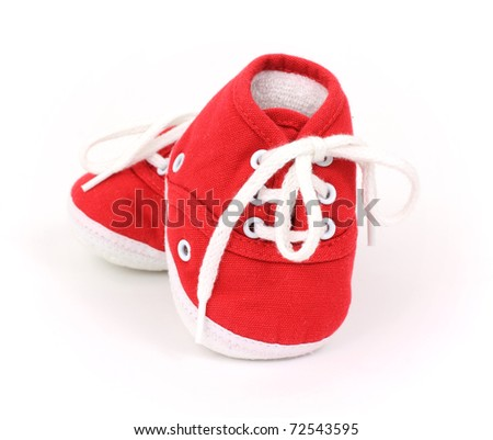A pair of red shoes for infants on a white background.