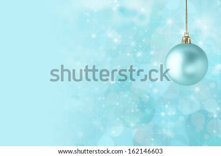 A pale turquoise blue Christmas bauble, suspended on gold string against a star filled twinkly bokeh background, fading into solid colour to provide copy space on the left side.
