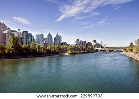 A pedestrian bridge across  Bow River in Calgary with skyscrapers in the background.