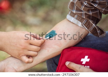 A person treating his friends wound with medicine