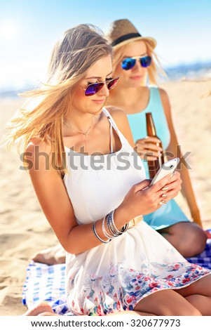 A picture of a group of friends drinking beer and texting on the beach