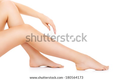 A picture of a young woman removing hair from  her legs over white background