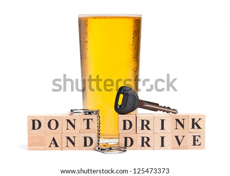 A pint of beer with a miniature pair of handcuffs and car key atop blocks spelling out Don't Drink and Drive isolated on a white background