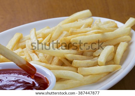 A plate full of delicious shoestring style french fries with ketchup