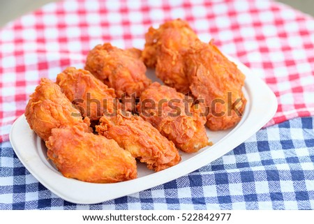 A plate of fresh, hot, crispy fried chicken on blue and red plaid towel