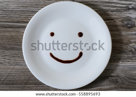 A plate with a smiling face on it written with chocolate
