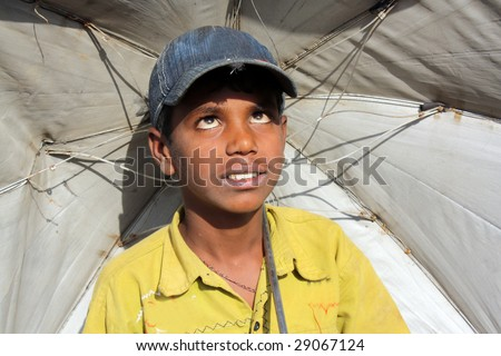 A poor Indian boy with an umbrella desperately waiting for the rains during the hot Indian summer.