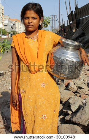 Poor Indian Teenage Girl Carrying A Pot Of Water On The Streetside