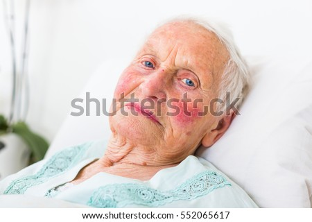 A portrait of a blue eyed elderly woman laying in bed.