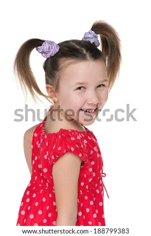 A portrait of a cheerful little girl looks back