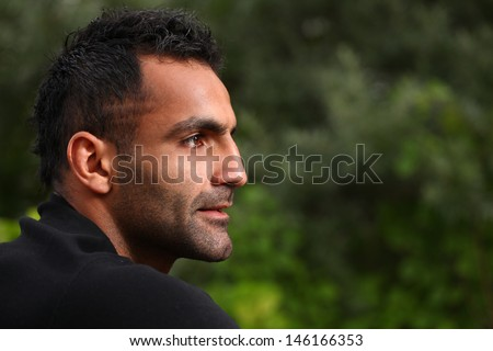 A portrait of a handsome man who is looking away while sitting near the trees