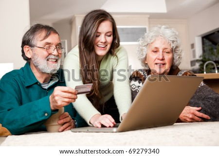 A portrait of a happy senior couple shopping online with the help from their granddaughter