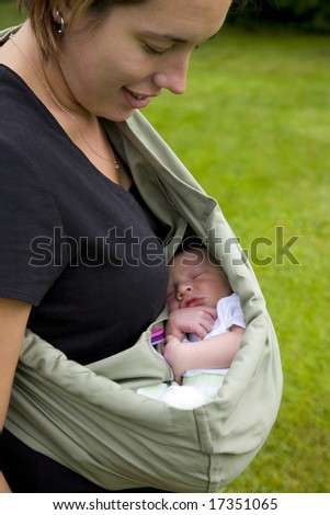 A portrait of a mother holding her newborn baby outside in a sling.