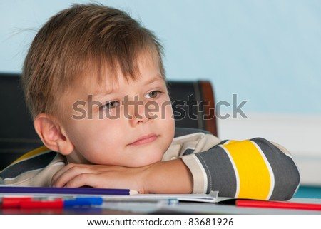 A portrait of a thoughtful little boy at the desk
