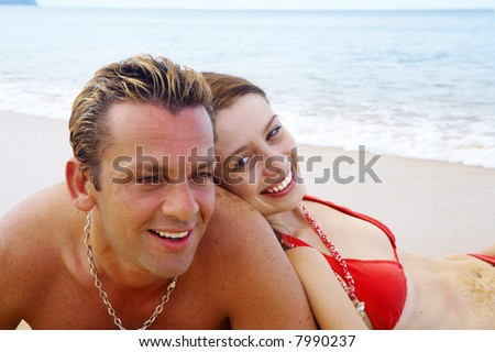 a portrait of attractive couple having fun on the beach. Focused on girl's face.