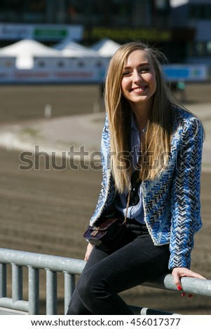 A portrait of smiling lady sitting on the handrails in a sunny day