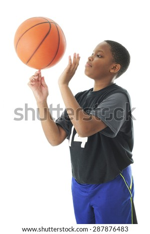 A preteen boy successfully spinning a basketball on an index finger.  Motion blur on the ball.   On a white background.