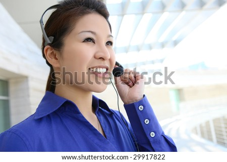 A pretty asian customer service business woman on phone