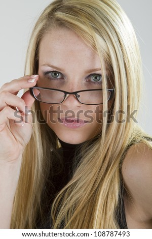 A pretty blond girl looking intently into the camera over her eyeglasses.