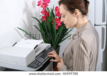 A pretty business woman making copies on the photocopy machine