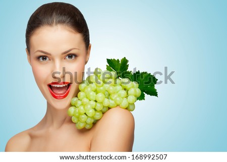 A pretty sexy woman holding a bunch of healthy green grapes on her naked shoulder.