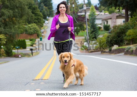 A pretty woman jogging with her golden retriever dog