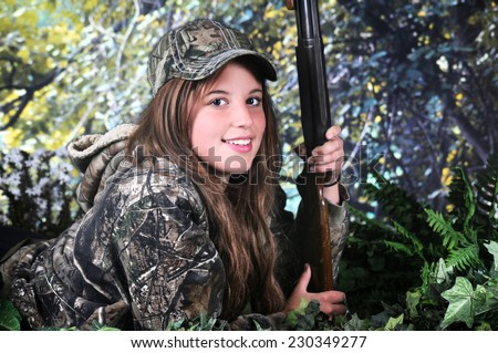 A pretty young teen hunter with a rifle looking at the viewer from her position on the ground surrounded by foliage.