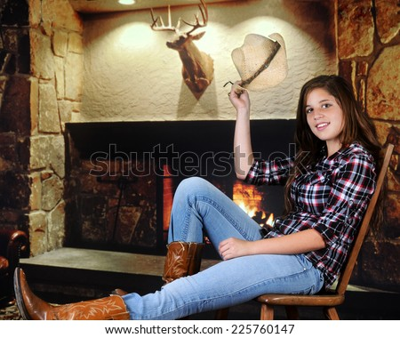 A pretty young teenage cowgirl tipping her hat in greeting as she rests near a fireplace.