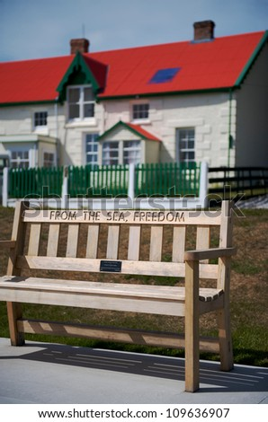 "A public bench on the waterfront in Port Stanley with the inscription ""From the sea, Freedom"" In the background is a typical Stanley dwelling with a red roof"