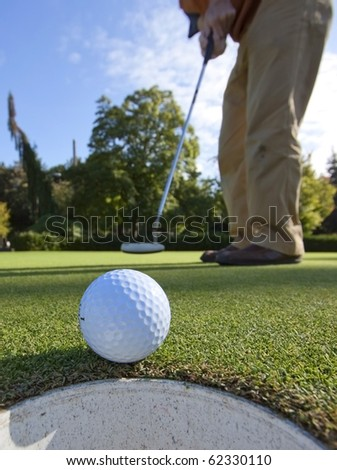 A putter dropping a short putt right into the cup