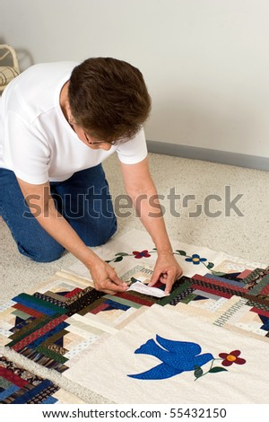 A quilter places a paper label on a panel of fabric prior to quilting.