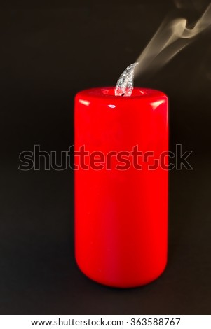 a red candle flame with water, smoke and black background