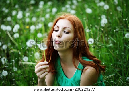 a red head girl blowing on a dandelion done with a vintage retro instagram filter