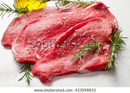 a red meat with rosemary on marble table