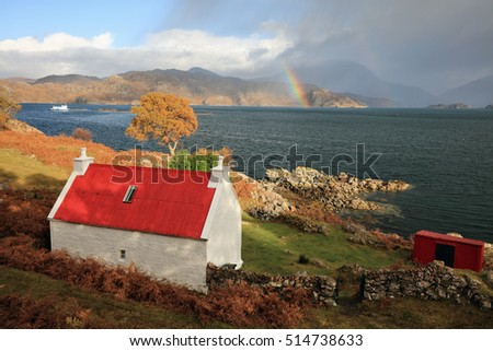 A red roofed cottage on a autumnal landscape with partial rainbow in the distance.