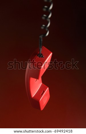 A red telephone receiver hanging on its cord