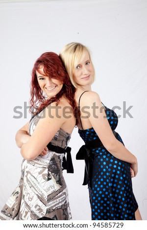 A redhead girl and her blond friend, standing back to back and smiling with joy