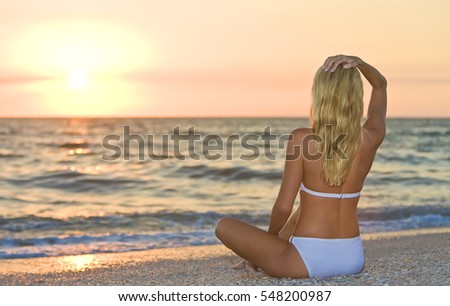 A relaxed sexy young blonde woman or girl wearing a bikini sitting on a deserted tropical beach at sunset or sunrise