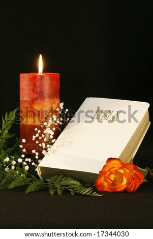 A religious still life photograph of a burning candle, babies breath, white bible and an orange rose over a black back drop, with room for copy.