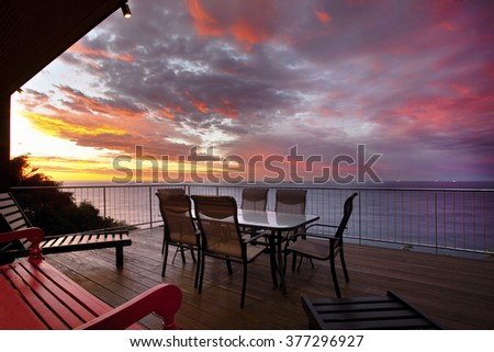 a residential deck with an ocean view at twilight