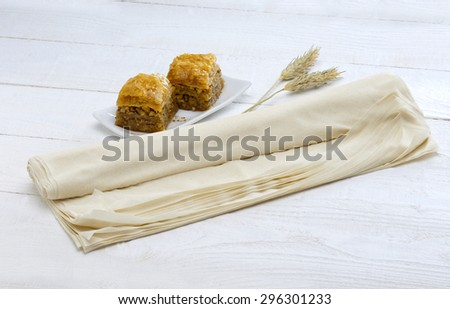 a roll of pastry or phyllo with two pieces of baklava served in a white plate(traditional oriental sweet)