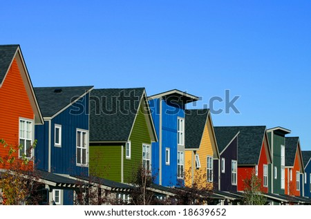 A row of colorful new houses against a blue sky