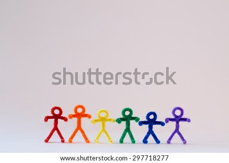 A row of rainbow colored, pipe-cleaner people. Great for international and multicultural purposes. With a white background, this photo has many applications for multiple ideas and concepts.