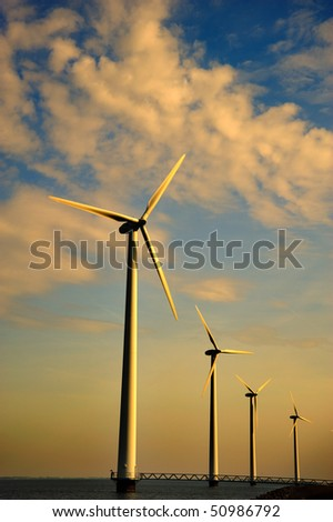 A row of wind turbines in the sea at sunset