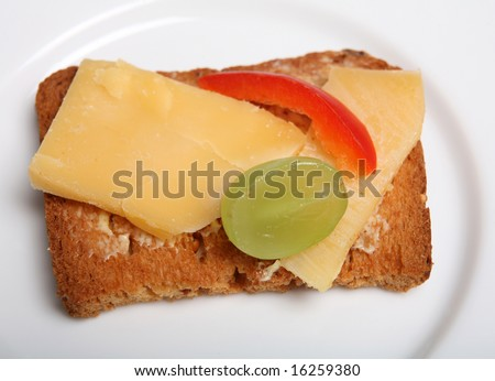 "A rusk or ""melba toast"" canape with dutch cheese, half a grape, a sliver of capsicum and a chive, on a white plate,"