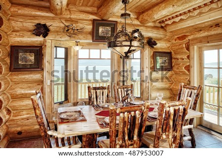 A rustic dining room, with comfortable furnishings, in a modern log cabin in the mountains.