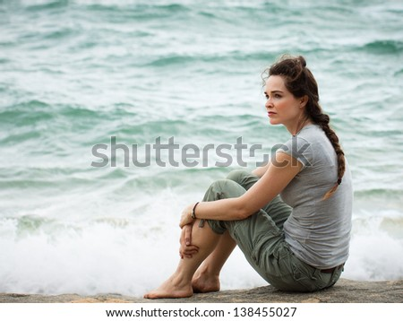 A sad and pensive woman sitting by the ocean deep in thought.