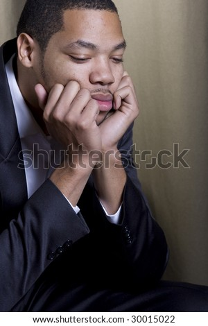 a sad businessman rests his hands on his chin