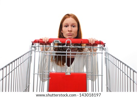 A sad shopping woman hanging behind her empty shopping cart.
